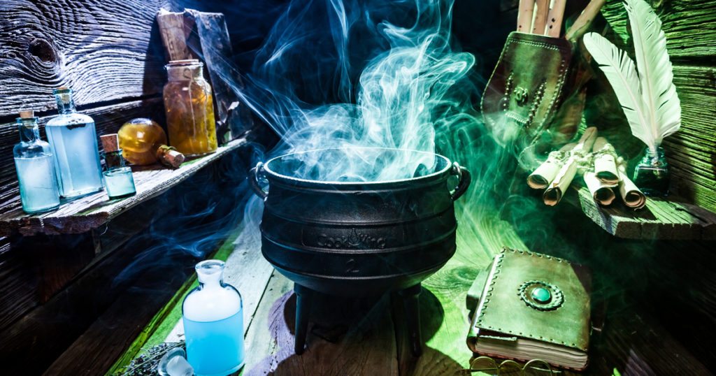 A cauldron filled with pale blue smoke sits amidst other accoutrements of witchcraft, shrouded in blue and green light.