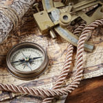 A collection of nautical items rest upon a desk: a sextant, map, rope and compass.