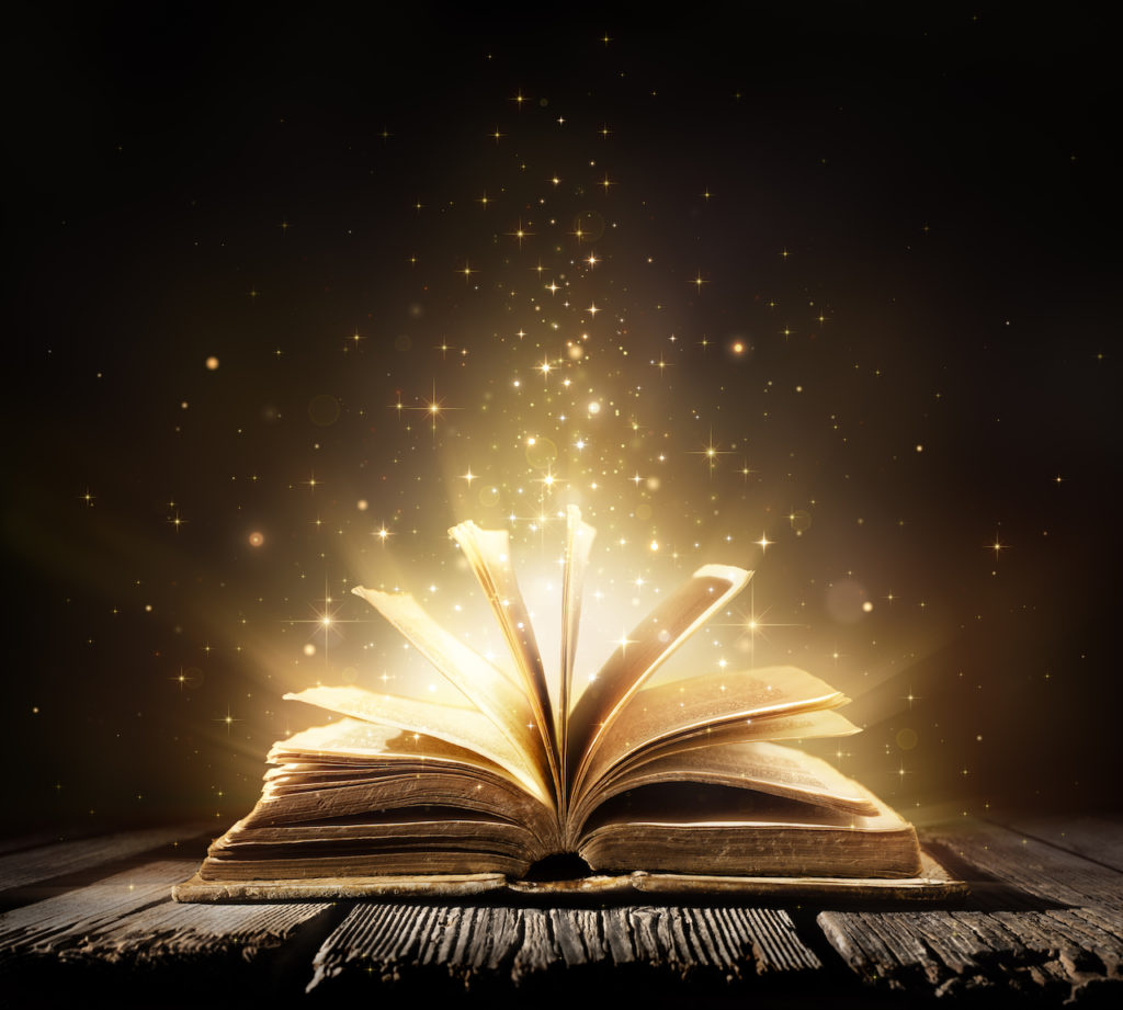 An open book against a dark background, light spilling from within