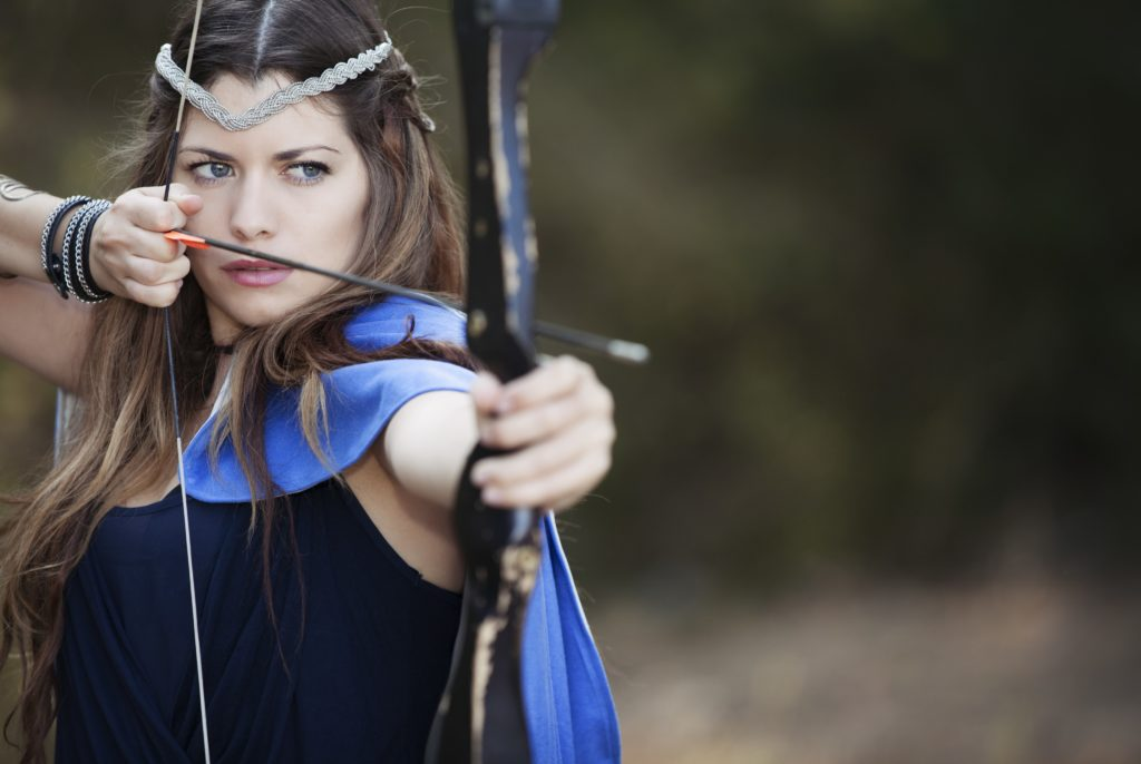 A woman with a circlet holds a bow in the drawn position.
