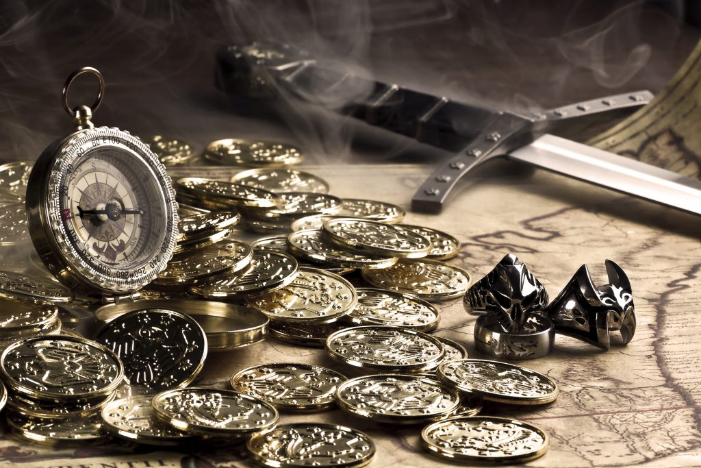 A pile of gold coins sits upon a table surrounded by trinkets.
