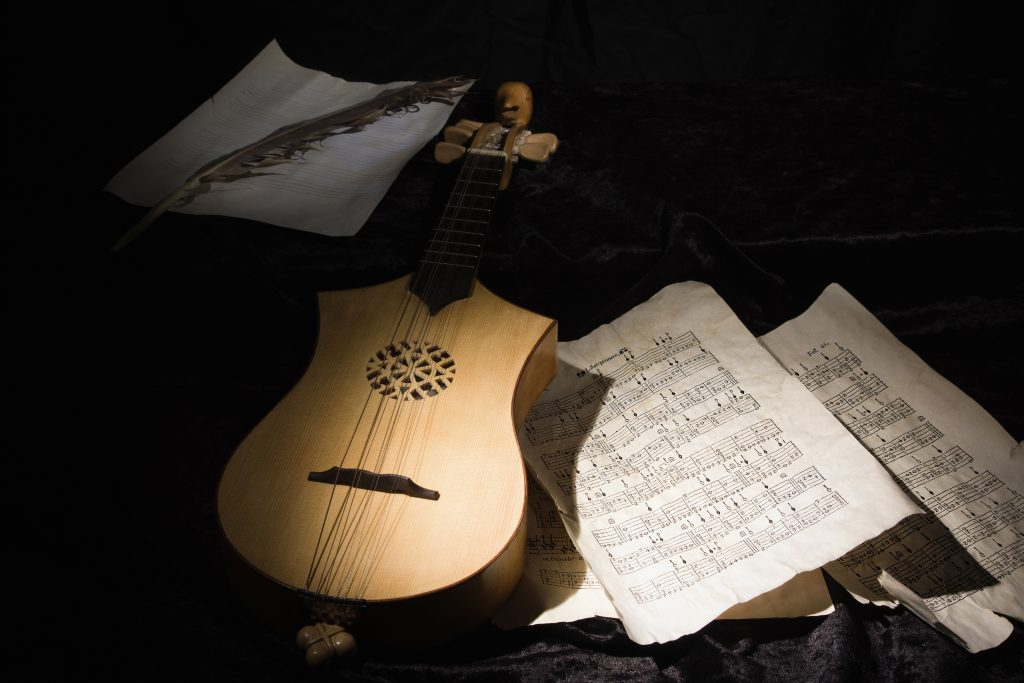 A mandolin lies among scattered music sheets in a half light