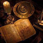 An old open book accompanied by a compass and a candle