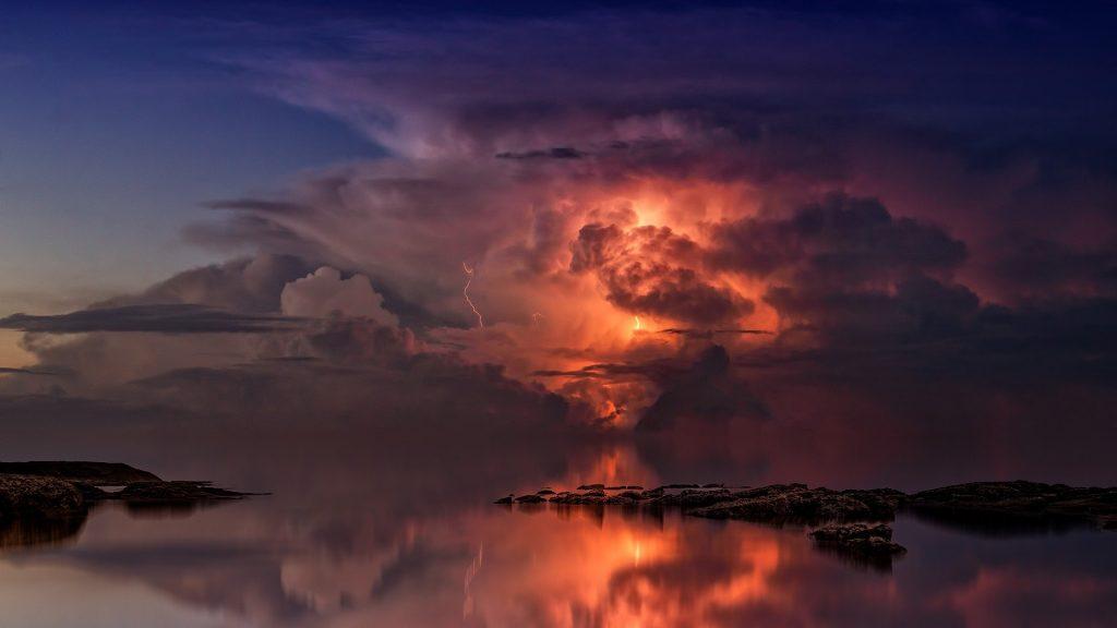 Thunderstorm over the sea, orange lightning lighting up its heart