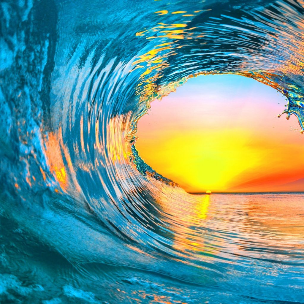 A wave arcs over itself against a sunset