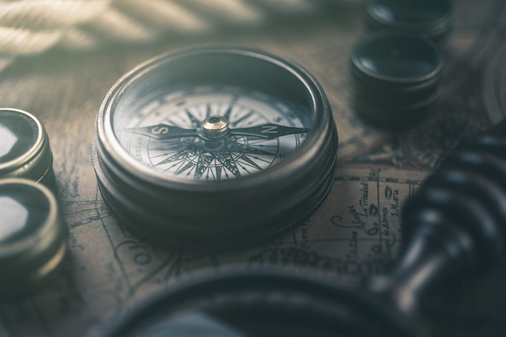 A compass lies upon a table with maps
