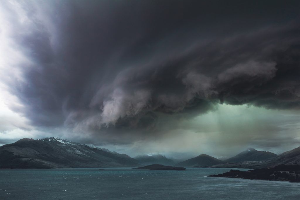 A dark storm gathers over a body of water