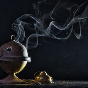 Upon a black background, a lone censer sits, smoking faintly.