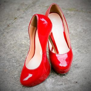 A pair of red high heeled shoes sits upon the floor.