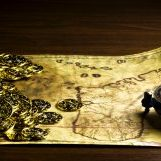A treasure map and coins sit upon a wooden table