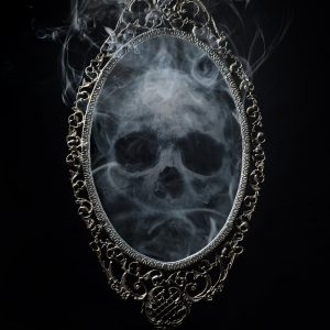 A mirror in an ornate frame against a black background, within the mirror a skull made of smoke lingers.
