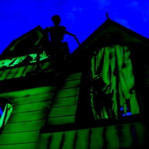 A spooky mansion, lit in green, looms ominously.