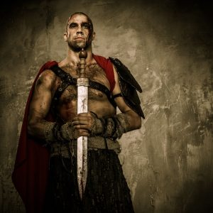 A warrior holding a blade stands proudly against a plain background.